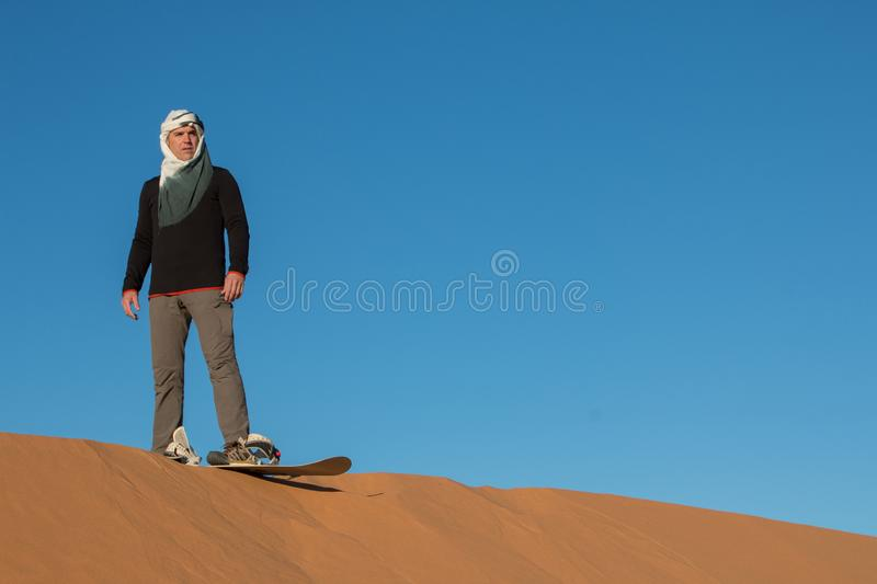 A man with a headscarf practicing sandboarding in the desert dunes of Erg Chebbi stock images