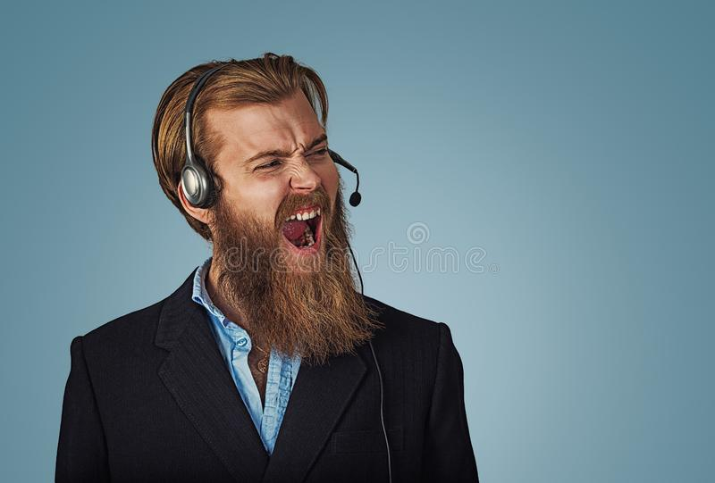Man with headset working as operator shouting with anger. Young adult hipster man with headset working as operator annoyed, frustrated shouting with anger, crazy stock photos