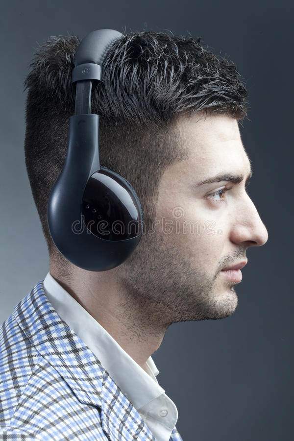 Man with headsets. Young man with headsets listening music stock image