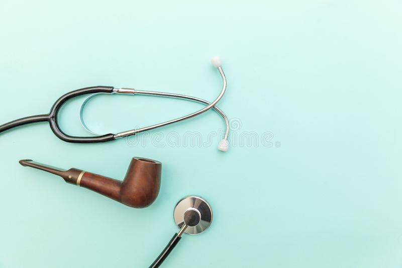 Man health care concept. Medicine equipment stethoscope or phonendoscope smoking pipe isolated on trendy pastel blue background. Man health care concept. Simply stock image