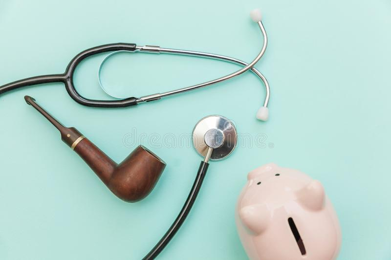 Man health care concept. Medicine equipment stethoscope or phonendoscope smoking pipe piggy bank isolated on trendy pastel blue. Man health care concept. Simply stock photography