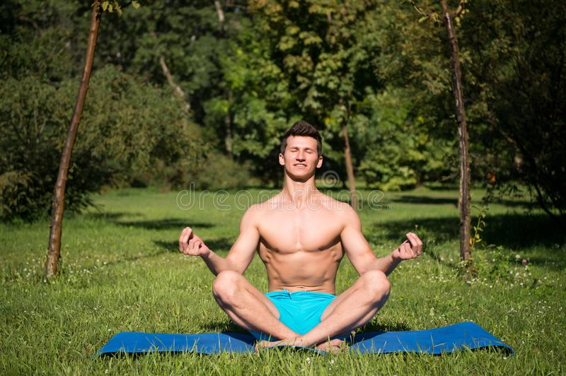 Man with healthy body meditate on yoga mat stock images