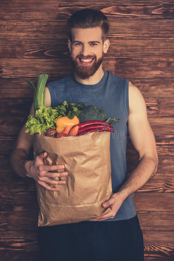 Man with healthy food. Handsome young bearded man in sportswear is holding a shopping bag full of healthy food, looking at camera and smiling, on wooden stock images