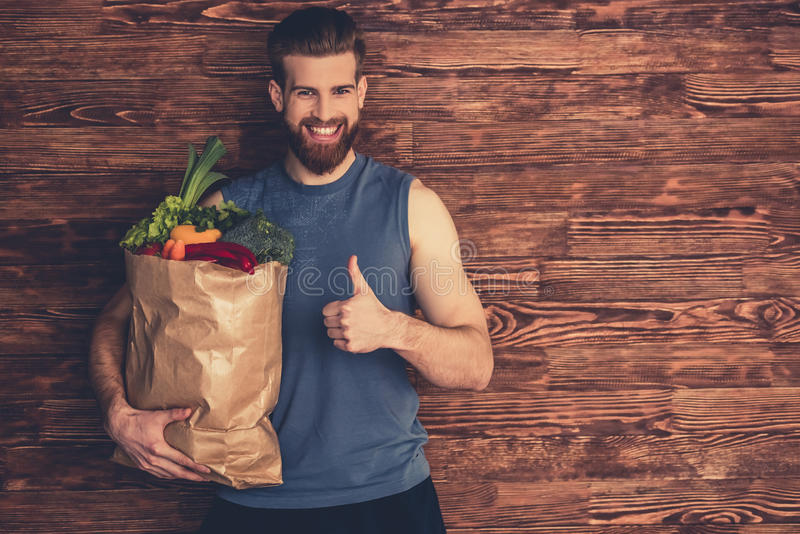 Man with healthy food. Handsome young bearded man in sportswear is holding a shopping bag full of healthy food, showing Ok sign and smiling, on wooden background royalty free stock image