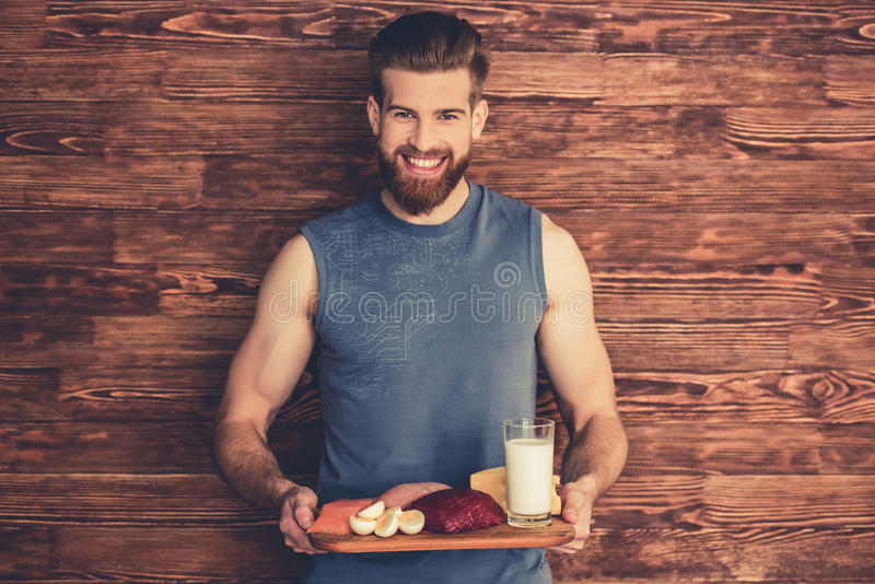 Man with healthy food. Handsome young bearded man in sportswear is holding a wooden tray with healthy food, looking at camera and smiling, on wooden background royalty free stock photography