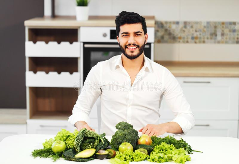 Man with Healthy Food. Happy handsome man in white shirt sitting at the table full of green healthy food royalty free stock images