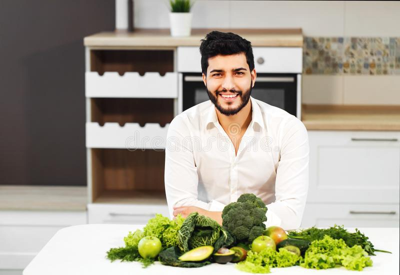 Man with Healthy Food. Happy handsome man in white shirt sitting at the table full of green healthy food royalty free stock photo