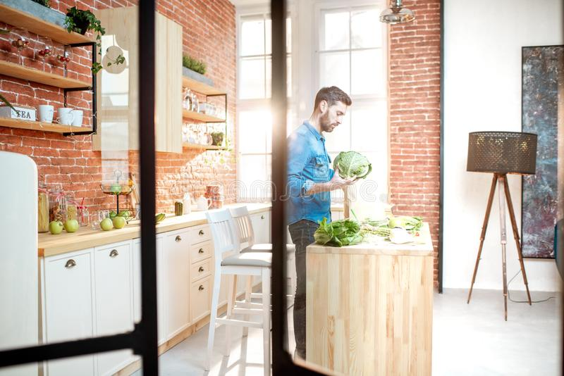 Man with healthy food on the kitchen. Man cooking healthy food standing on the kitchen of the beautiful loft apartment royalty free stock image
