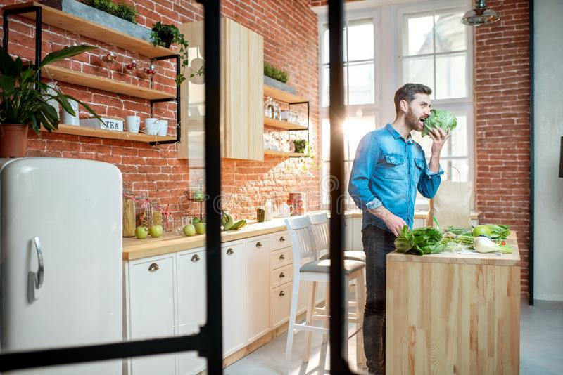 Man with healthy food on the kitchen. Man cooking healthy food standing on the kitchen of the beautiful loft apartment stock photos