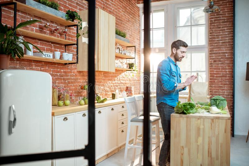 Man with healthy food on the kitchen. Man cooking healthy food standing on the kitchen of the beautiful loft apartment stock photo