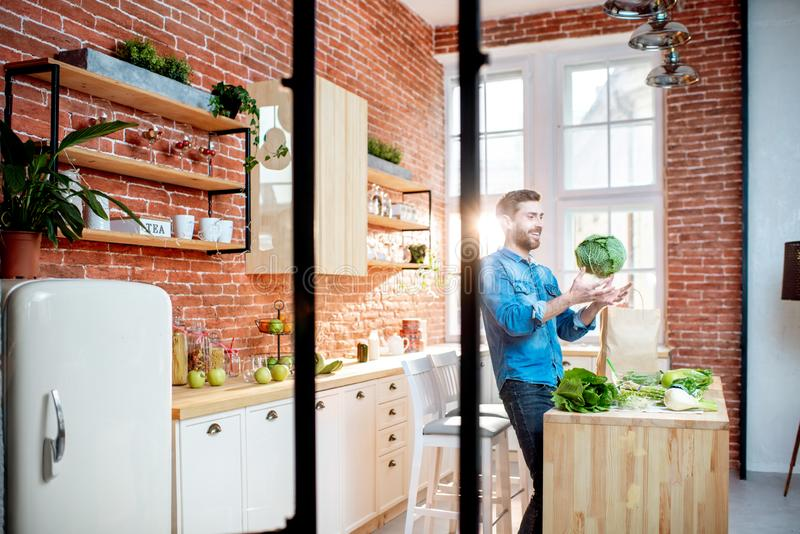 Man with healthy food on the kitchen. Man cooking healthy food standing on the kitchen of the beautiful loft apartment royalty free stock photography