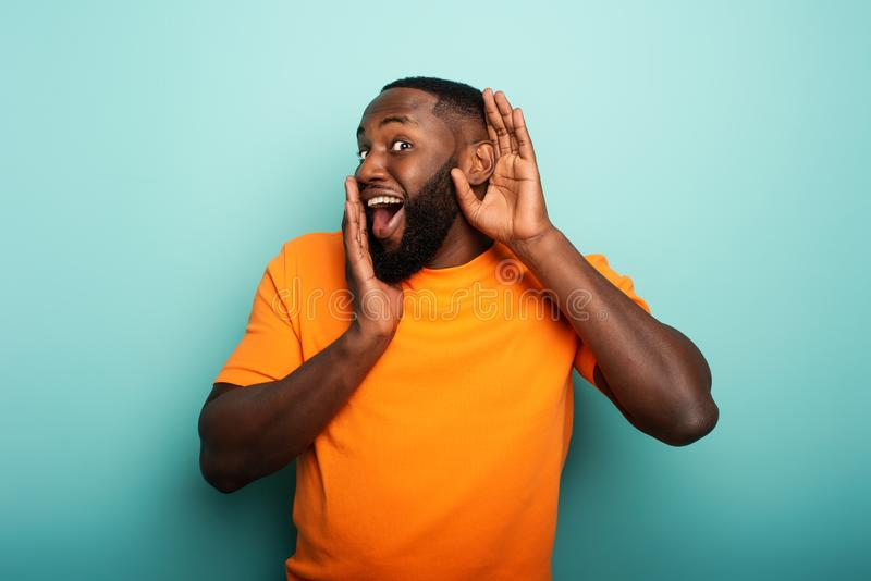 Man hears a secret notice. Concept of curiosity and gossip. Amazed expression. Black man hears a secret notice. Concept of curiosity and gossip. Amazed stock image