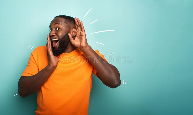 Man hears a secret notice. Concept of curiosity and gossip. Amazed expression. Black man hears a secret notice. Concept of curiosity and gossip. Amazed royalty free stock image