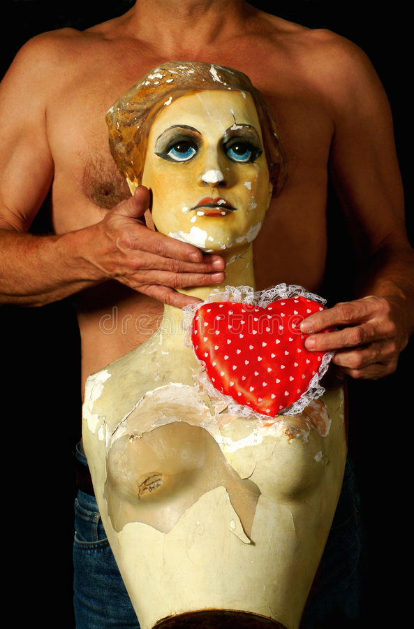 Man and heart. A body of a man and a figurine of a woman, with a red heart shaped cushion in his hand on black background stock photos