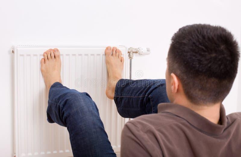 Man heating feet on radiator. Young man heating his bare feet on radiator on wall stock image