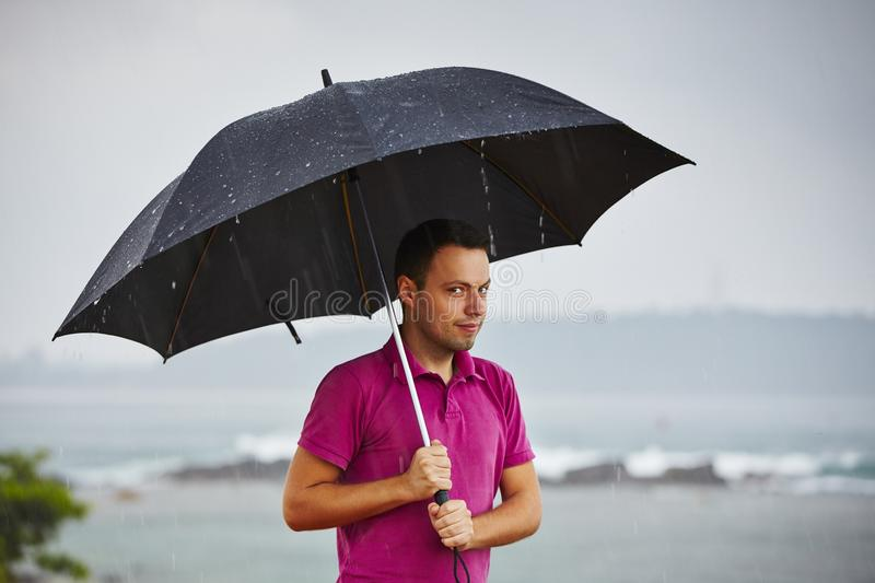 Man in heavy rain. Man with black umbrella in heavy rain royalty free stock image