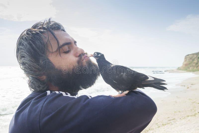 Man kissing pigeon royalty free stock image