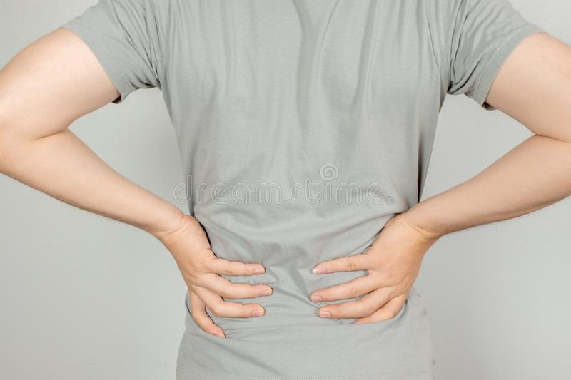 A man held her hand behind him with back pain. Healthcare concept stock images