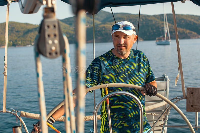 Man at helm leads a sailing yacht in the sea. Sport. royalty free stock photo