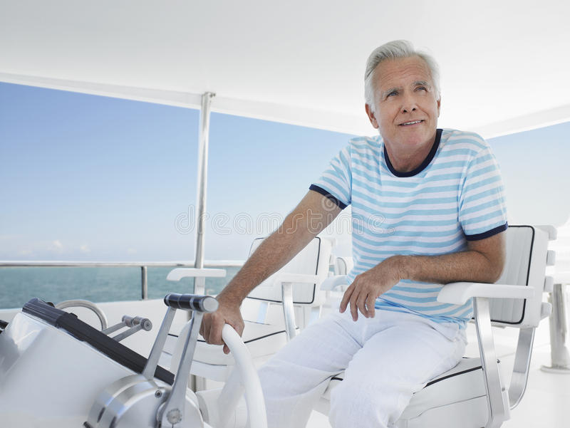 Man At The Helm Of Luxury Yacht. Happy middle aged man sitting at helm of luxury yacht royalty free stock images