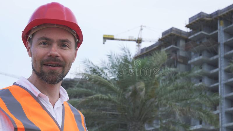Man in a helmet, architect, engineer, manager tells about the progress of construction in evening stock images