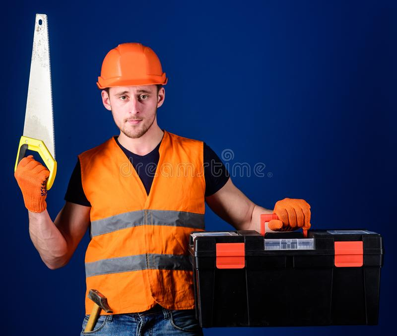 Man in helmet, hard hat carries toolbox and holds handsaw, blue background. Worker, repairer, repairman on serious face. Carries toolbox, ready for repair, copy royalty free stock photos