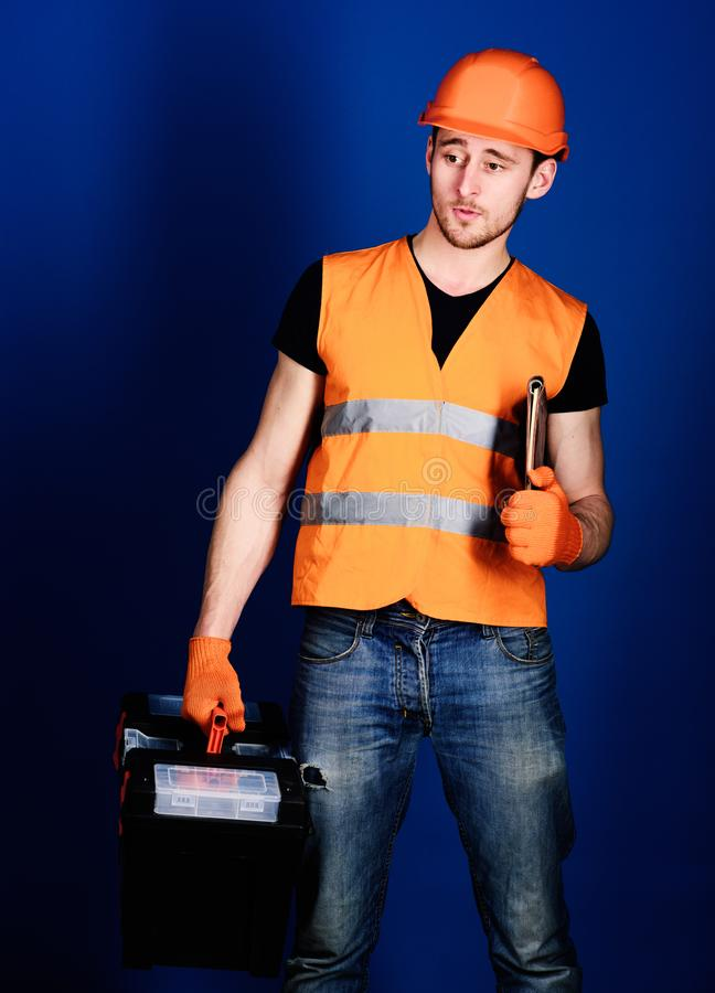 Man in helmet, hard hat holds toolbox and folder with documents, blue background. Worker, repairer, builder on dreamy. Face carries case with tools. Repair stock image