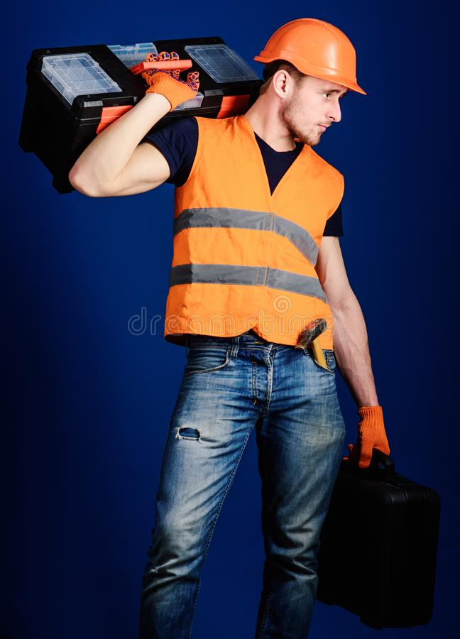 Man in helmet, hard hat holds toolbox and suitcase with tools, blue background. Repair service concept. Worker, repairer. Repairman, builder on calm face stock photos