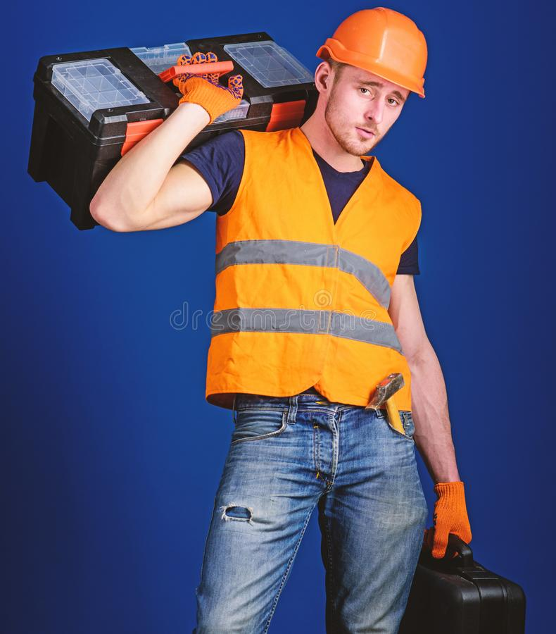 Man in helmet, hard hat holds toolbox and suitcase with tools, blue background. Worker, repairer, repairman, builder on stock photo