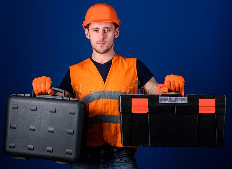 Man in helmet, hard hat holds toolbox and suitcase with tools, blue background. Worker, repairer, repairman, builder on royalty free stock images
