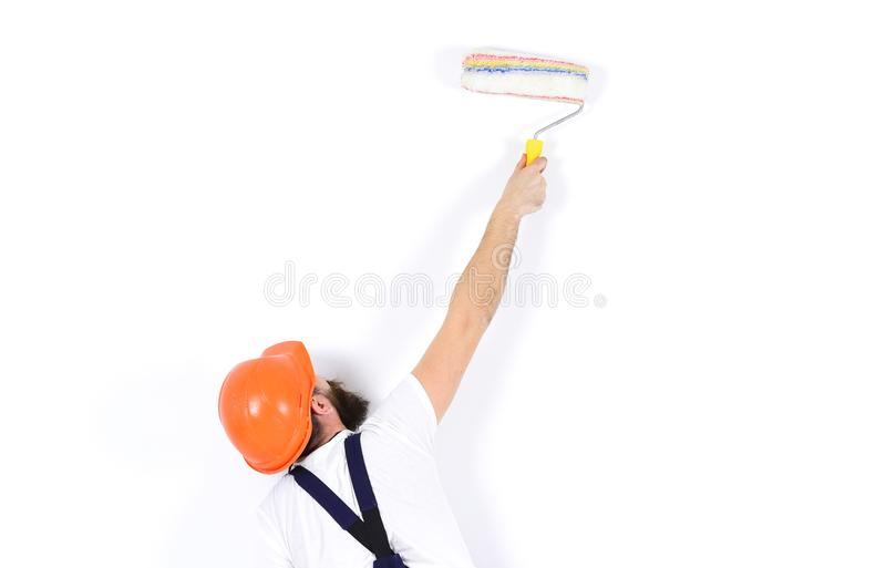 Man in helmet with paint roller, rear view, copy space. Renovation and decoration concept. Painter, decorator stock photos