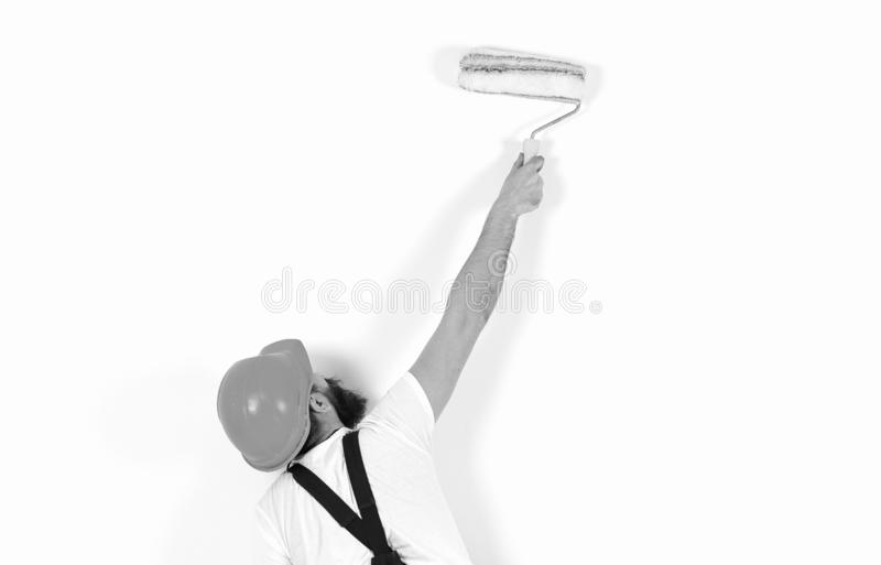Man in helmet with paint roller, rear view, copy space. Renovation and decoration concept. Painter, decorator stock photo