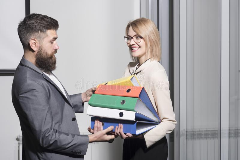 Man help woman to carry binders in office. Businesswoman and businessman with folders. Bearded man and girl with stock photos