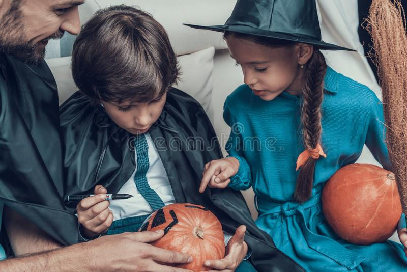Man helping Children in Costumes to Carve Pumpkin royalty free stock photos