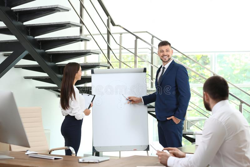 Man helping his colleague to give presentation on meeting stock images