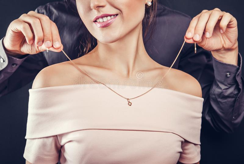 Man helping his girlfriend to try on a golden necklace. Gift for Valentines day. stock photography