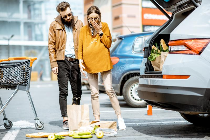 Man helping pregnant woman at the supermarket parking. Man helping young pregnant women feeling bad on the parking place near the supermarket royalty free stock image