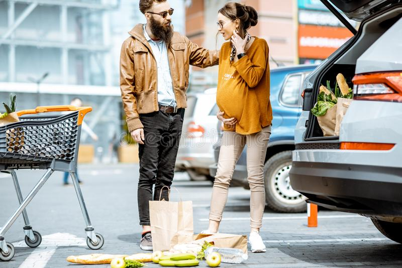 Man helping pregnant woman at the supermarket parking. Man helping young pregnant women feeling bad on the parking place near the supermarket royalty free stock images