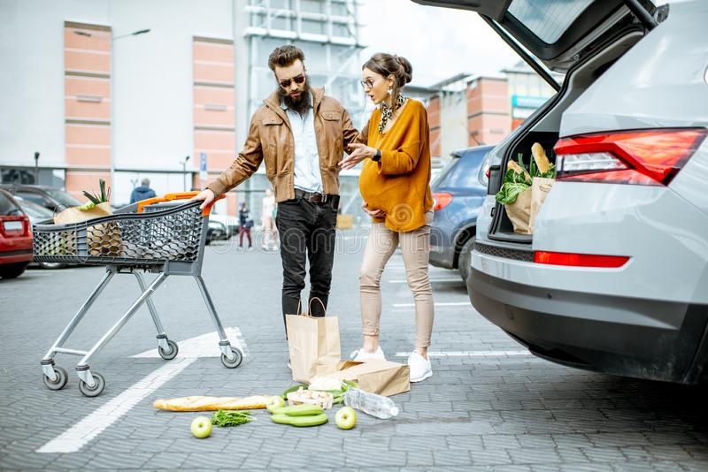 Man helping pregnant woman at the supermarket parking. Man helping young pregnant women feeling bad on the parking place near the supermarket stock images