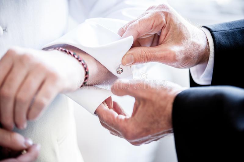 Man helping putting on the shirt cufflinks royalty free stock image