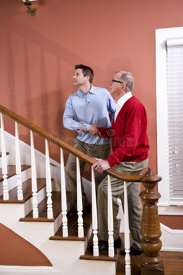 Download Man Helping Senior Father Climb Stairs At Home Stock Image - Image: 14552299