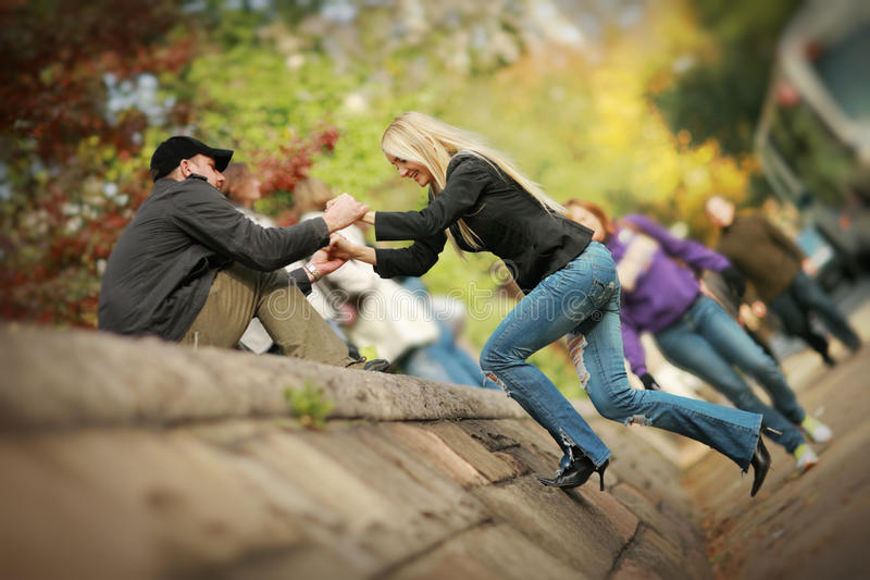 Man helping woman. To climb wall in park stock images