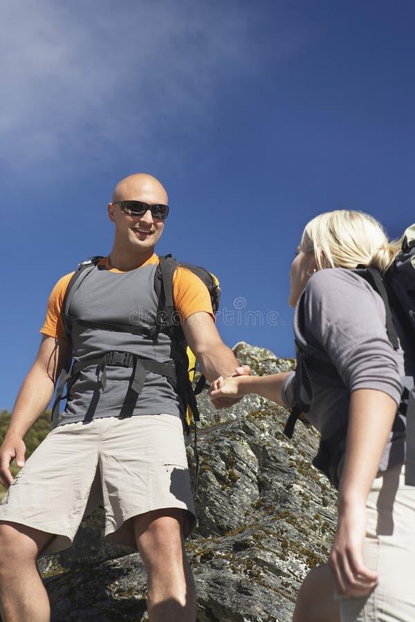 Download Man Helping Woman Climb Onto A Boulder Stock Image - Image: 31830009