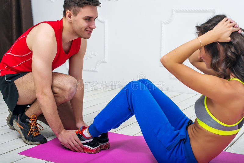 Man helping a woman or girl in making abdominal stock photos