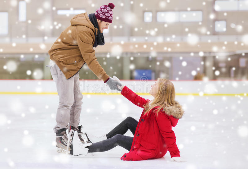 Man helping women to rise up on skating rink. People, friendship, sport and leisure concept - smiling men helping women to rise up on skating rink royalty free stock photo