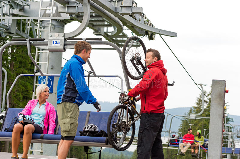 Download Man Helping Couple Holding Bicycle Chair Lift Stock Photo - Image: 29933038