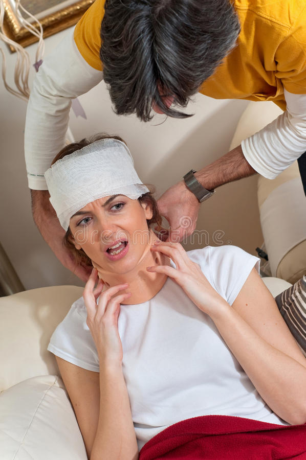 Man Helps Injured Woman with her Neck Brace. A man helps an injured woman wearing a neck brace and with bandages on her head as she tries to get comfortable. He royalty free stock photography