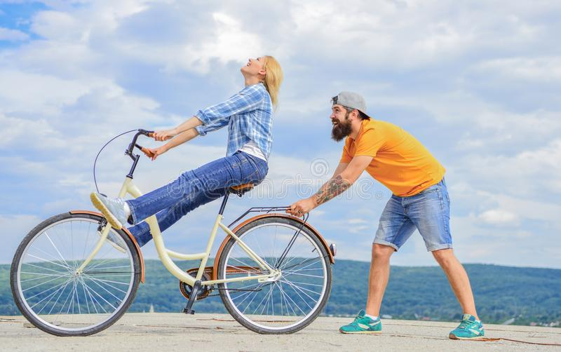 Man helps keep balance and ride bike. How to learn to ride bike as adult. Girl cycling while boyfriend support her stock photo