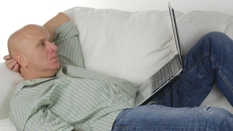 Man hemma som sitter och vilar på Sofa Doing Business Using en bärbar dator royaltyfria foton