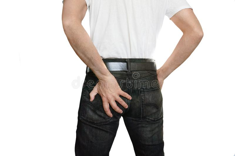 Man with hemorrhoids. Guy with pain in black jeans holding his with his left hand on a white isolated background royalty free stock photos